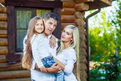 Happy young family near the wooden house Stock Images