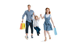 Happy young family with one child holding shopping bags. And smiling at camera isolated on white stock photo