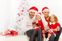 Happy young family opening presents on Christmas Royalty Free Stock Photo