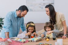 happy young family painting eggs for easter stock image