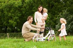 Happy young family in park with bicycle. Portrait of happy young family in park with bicycle stock photography