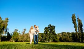 Happy young family in the park on a sunny day. Parent with child in nature royalty free stock photography