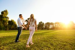Happy young family in the park at sunset. Happy young family in the park at sunset in the summer autumn royalty free stock photo