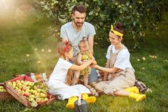 The happy young family during picking apples in a garden outdoors Stock Photo