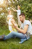 The happy young family during picking apples in a garden outdoors Royalty Free Stock Images