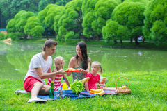 Happy young family picnicking outdoors. Happy cute family of four picnicking outdoors Stock Photos