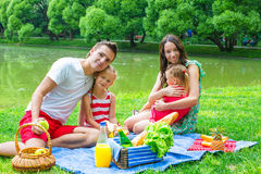 Happy young family picnicking outdoors near the Stock Photos