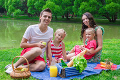 Happy young family picnicking outdoors near the Royalty Free Stock Photography