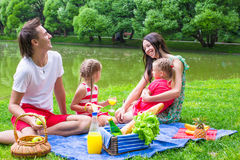 Happy young family picnicking outdoors near the Stock Image