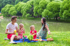 Happy young family picnicking outdoors near the Royalty Free Stock Photos