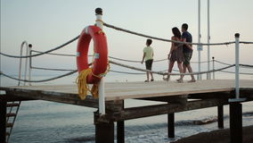 Happy young family on the pier by the sea stock footage