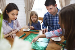 Happy young family plaing board game Royalty Free Stock Photos