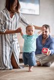 Happy young family playing and baby learning to walk at home. Happy young family playing and baby boy learning to walk at home stock image
