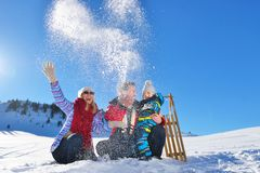 Happy young family playing in fresh snow at beautiful sunny winter day outdoor in nature Royalty Free Stock Image