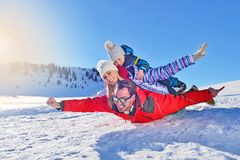 Happy young family playing in fresh snow at beautiful sunny winter day outdoor in nature Royalty Free Stock Photo