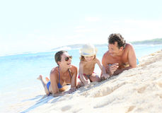 Happy young family playing on a sandy beach Royalty Free Stock Photo
