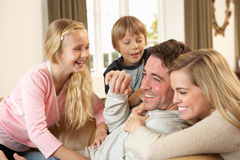Happy young family playing together on sofa Royalty Free Stock Image