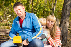 Happy young family posing together outdoors Stock Photos