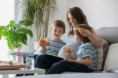 Happy young family, pregnant mother and two boys, eating tasty p