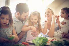 Happy young family preparing salad together. stock image