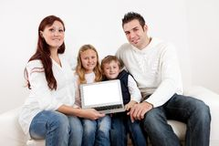 Happy young family presenting laptop Stock Photography