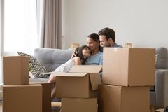 Happy family with daughter relax on couch on moving day. Happy young family relax together on couch in living room among cardboard boxes cuddle on moving day stock photography