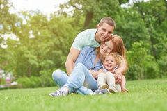 Happy young family relaxing at the park. Happy young men smiling joyfully embracing his beautiful wife and daughter sitting on the grass together copyspace Stock Images