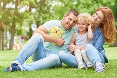 Happy young family relaxing at the park. Shot of a happy young family sitting on the grass at the park together smiling to the camera copyspace lifestyle leisure Stock Photo