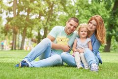 Happy young family relaxing at the park. Young beautiful women sitting on the grass with her happy husband and adorable little daughter copyspace love family Stock Image