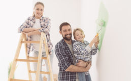Family painting a room together. Happy young family renovating their home, the father is holding his son and he is helping him to paint a wall with a paint Royalty Free Stock Images