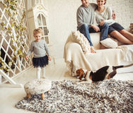 Happy young family resting in living room on Sunday. Happy parents and young daughter resting in the living room on Sunday Royalty Free Stock Photo