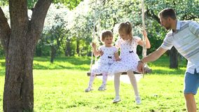Happy young family riding their girls on swing in spring season garden. stock footage