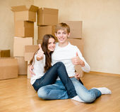 Happy young family showing thumbs up on a background of cardboard Stock Images