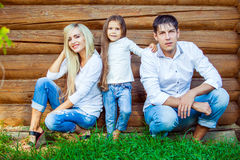 Happy young family sits near the wooden house Royalty Free Stock Image