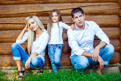 Happy young family sits near the wooden house Stock Image