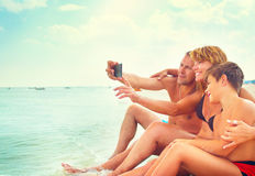 Happy young family sitting on the beach and taking selfie Stock Photography