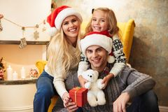 Happy young family sitting in chair, looking at camera while cel stock images