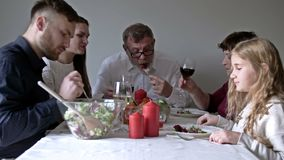Happy young family sitting by festive table and eating traditional Thanksgiving food