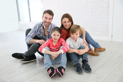 Happy young family sitting on the floor at home Royalty Free Stock Photo