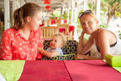 Happy young family sitting at table in beach cafe during summer holidays Royalty Free Stock Photo