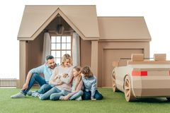Happy young family sitting on yard of cardboard house with their puppy. Isolated on white stock image