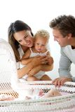 Happy young family smiling at baby in cot Royalty Free Stock Images