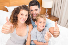 Happy young family smiling at camera on bed giving thumbs up Stock Image