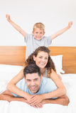 Happy young family smiling at camera on bed posing Royalty Free Stock Photos