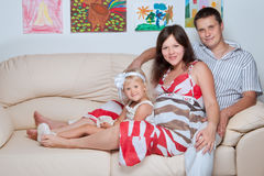 Happy young family on sofa in home Stock Image