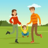 Happy young father and mother spending time with son. Happy young family spending time in city park. Child jumping and holding hands of parents. Father, mother Royalty Free Stock Photo