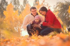 Happy young family spending time outdoor in the autumn park Royalty Free Stock Photos