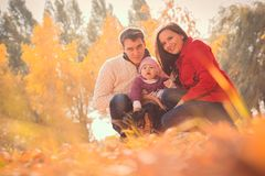 Happy young family spending time outdoor in the autumn park Royalty Free Stock Images