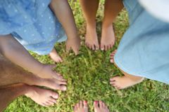 Happy young family spending time outdoor on a summer day. Feet on the grass. Top view royalty free stock photos