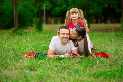 Happy young family spending time outdoor on summer day. Happiness and harmony in family life. Family fun outside stock photos